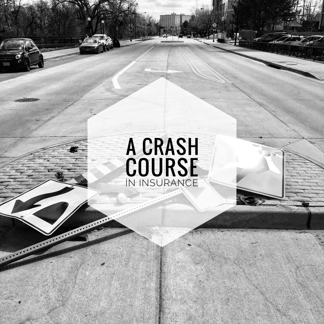 """A street with two knocked over street signs and the words """"a crash course in insurance"""" overlaid"""